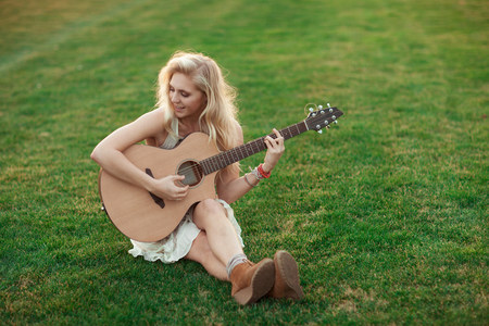 Woman playing guitar in grass LANG_EVOIMAGES
