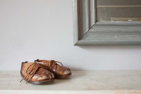 Brown leather shoes on mantelpiece LANG_EVOIMAGES