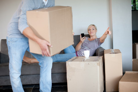 slacker: Young woman moving house on sofa directing man with box