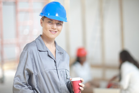 Smiling female construction worker with coffee