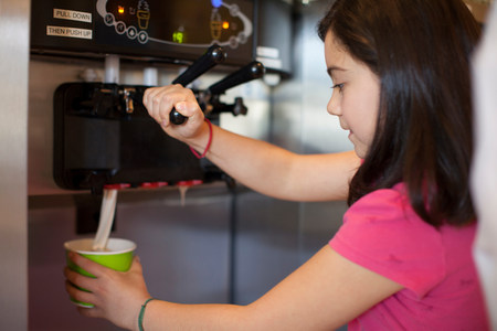 tempted: Girl pouring cup of frozen yogurt