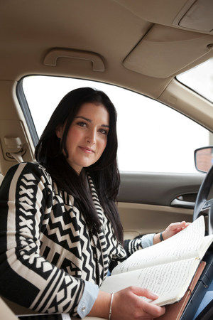 tomes: Young woman in car with notebook