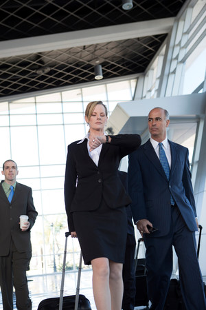 Businesspeople walking through airport with suitcases LANG_EVOIMAGES