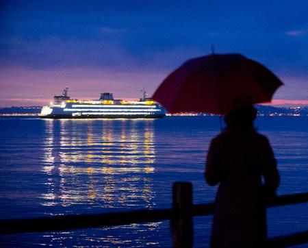 Woman with umbrella admiring cruise ship