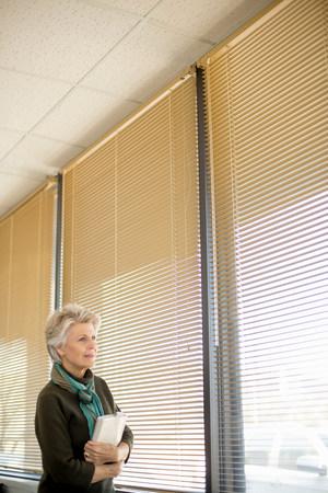 ponderous: Senior woman looking through window