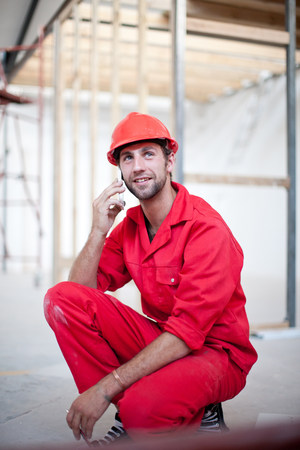 Builder on construction site on mobile phone