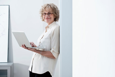 Businesswoman using laptop in office LANG_EVOIMAGES