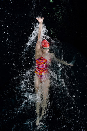 exerting: Teenage girl doing backstroke in swimming pool