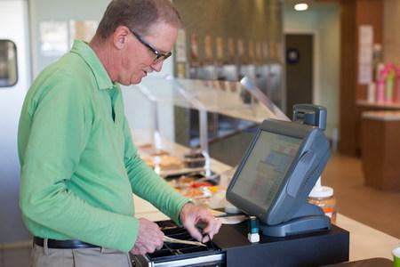 cash register building: Cashier operating till in store LANG_EVOIMAGES