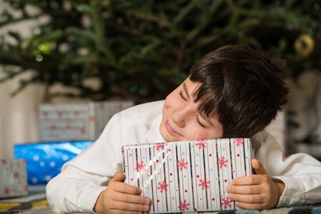 buen vivir: Niño abrazándose regalo de Navidad