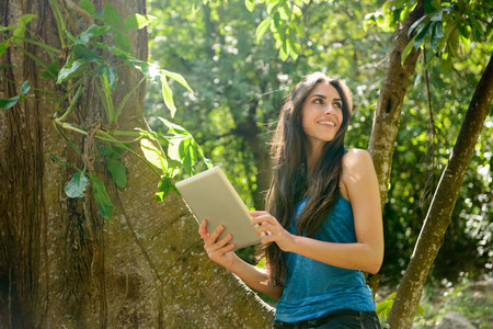 turning the page: Woman using tablet computer in jungle