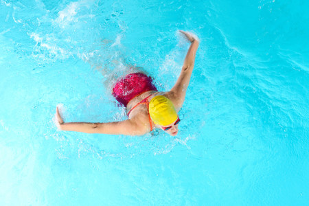 exerting: Mature woman doing butterfly stroke in swimming pool