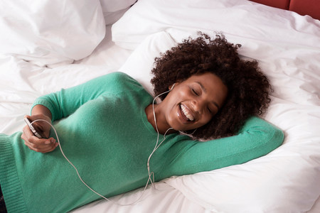 snug: Woman listening to earphones on bed LANG_EVOIMAGES