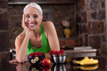 Older woman having fruit in kitchen LANG_EVOIMAGES