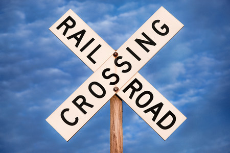 leisurely: Railroad crossing sign under blue sky LANG_EVOIMAGES