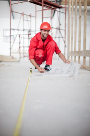 Erbauer mit messendem Boden des blauen Druckes auf Baustelle