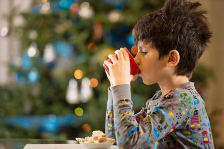 pyjama: Boy having milk and Christmas cookies