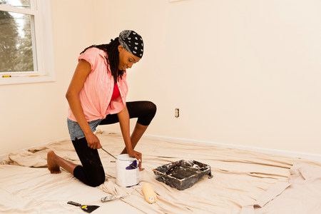self sufficient: Woman painting in new home LANG_EVOIMAGES