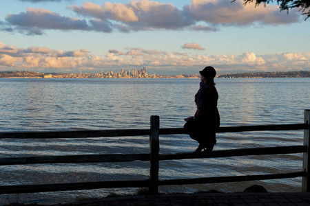 sit down: Silhouette of woman sitting on fence