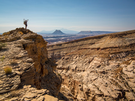San Rafael Swell: Hiker cheering on rocky hilltop LANG_EVOIMAGES