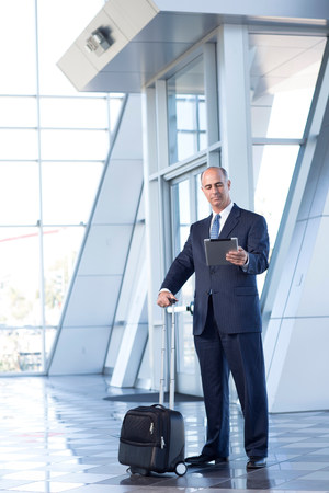 Mature businessman with digital tablet and suitcase