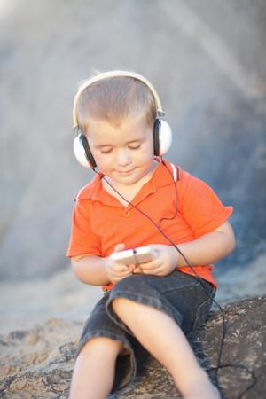 sit down: Boy sitting on rocks wearing headphones