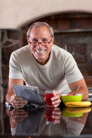 60 64 years: Older man reading newspaper at breakfast