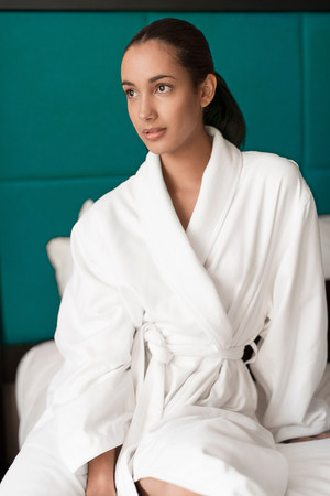 Woman in bathrobe sitting on bed