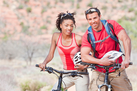 getting out: Couple smiling on mountain bikes LANG_EVOIMAGES