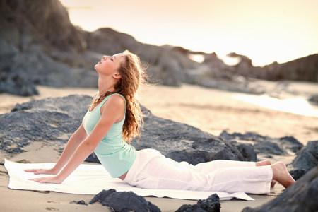 Young woman doing yoga on beach