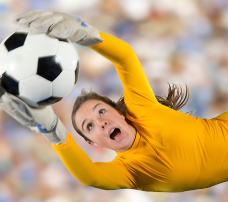 Soccer player catching ball in air LANG_EVOIMAGES
