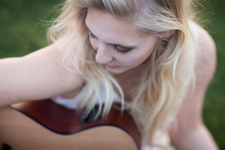 above 18: Woman playing guitar in grass LANG_EVOIMAGES