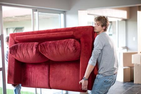 exerting: Young men carrying sofa