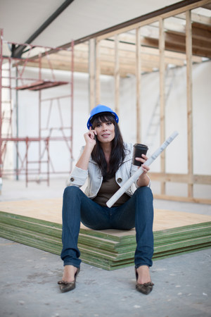 housebuilding: Portrait of woman holding blueprint on cell phone LANG_EVOIMAGES