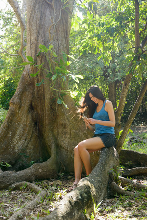 Woman using cell phone in jungle
