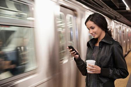 check ups: Woman using cell phone at subway station
