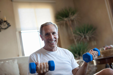 energy work: Older man lifting weights at home