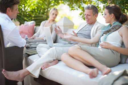 45 50: Casual business people on patio using laptop