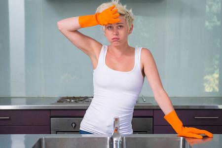 Young woman wearing orange washing up gloves