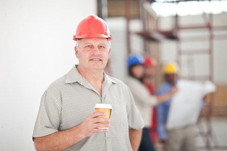 matures: Portrait of a builder having a coffee break