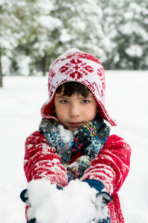 wintry weather: Boy holding snowball outdoors