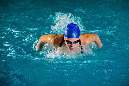 Teenage girl in swimming cap and goggles swimming in pool