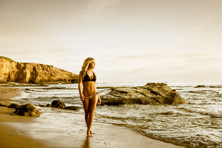 secluded: Young woman in bikini walking along beach LANG_EVOIMAGES