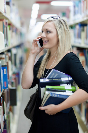 Female student on smartphone holding pile of books LANG_EVOIMAGES
