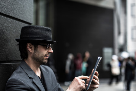 shadowed: Portrait of man using digital tablet on city street