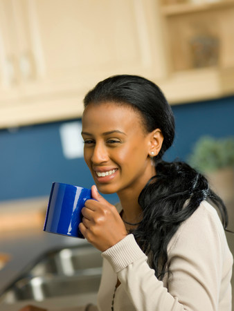 Young woman holding cup and smiling
