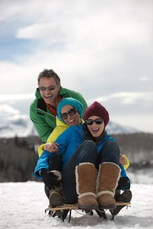 to go sledding: Three friends sitting on sledge in snow