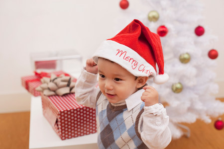 3 year old: Boy wearing Santa hat in front of Christmas decorations