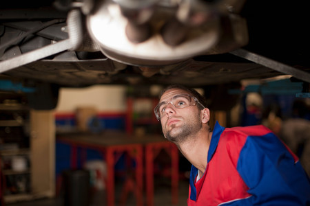 Car mechanic at work in service bay