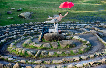 arms lifted up: Mid adult dancers performing with red umbrellas in stone circle